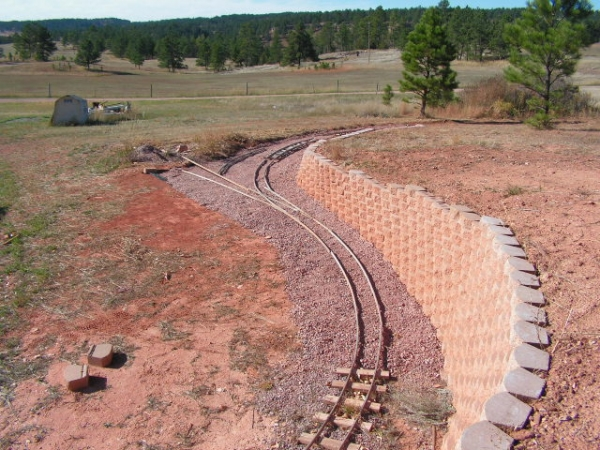 "Here is a photo of the ""top end"" of the line as it is.  After I finished the retaining wall, I put down weed block fabric and sub-ballast and then laid out some rail and a set of points to get an idea of the next stage of track laying.  The main line will go around towards the right, and the straight track will lead to a ""dock"" area, where visitor's stock can be unloaded.